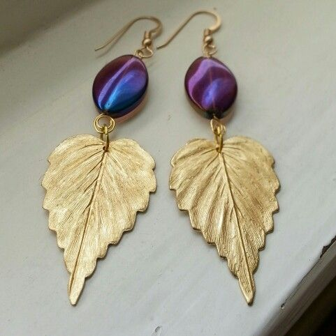 Sweet and simple leaf earrings enhanced with iridescent purple glass beads.