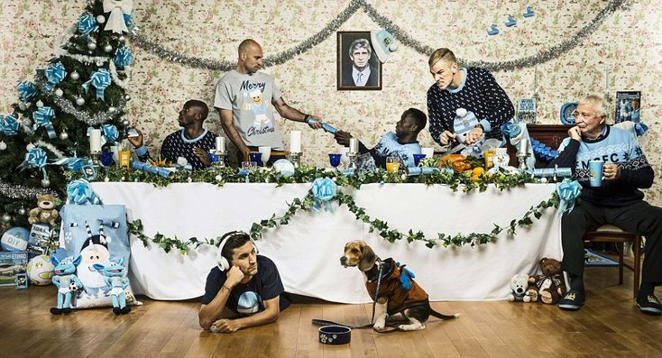 Manchester City's players pose for a photo around the Christmas table, including (clockwise from top left) centre back Eliaquim Mangala, goalkeeper Willy Caballero, right back Bacary Sagna, keeper Joe Hart, club legend Mike Summerbee, Pongo Bongo - dog of City employee Anne-Marie - and winger Jesus Navas