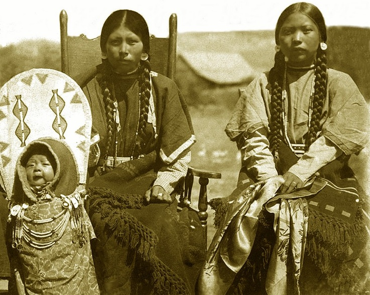 """Two Nez Perce women sit beside a baby in a cradleboard. The woman on the left is the first wife of Willie """"Red Star"""" Andrew. The woman on the right is Anne Kamiakin. She wears similar clothing to the other woman but she hold in hands a silken cloth. The baby in cradleboard is unidentified."""