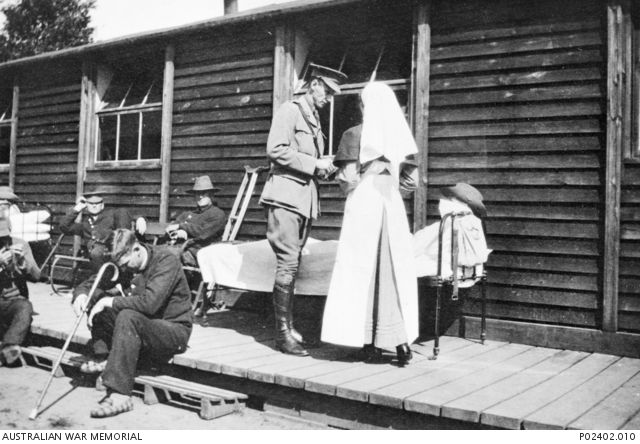 The original caption reads `Major Cameron conducts his rounds'. Major Cameron (probably Donald Allan Cameron AAMC), and a nurse stand beside a patient (in a slouch hat) lying in a bed outside a ...