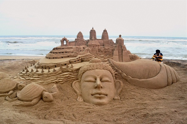 Sand artist Sudarshan Pattnaik giving final touch to his sculpture, 'Welcome Odisha' at Puri beach. (PTI)