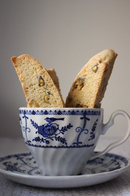 Lemon Pisachio Biscotti  Adapted from Tyler Florence  Makes 24 cookies    1 1/2 cups shelled pistachios  1/2 cup unsalted butter  3 eggs  1 cup sugar  1 teaspoon vanilla extract  Zest of 2 lemons  3 1/2 cups all-purpose flour  1 teaspoon baking powder  1/2 teaspoon salt*    Preheat oven to 350 degrees F. Spread the pistachios on a baking sheet into a single layer. Bake for 10 minutes or until the nuts are lightly toasted.    Cream together the butter and sugar until light and fluffy. Add the…