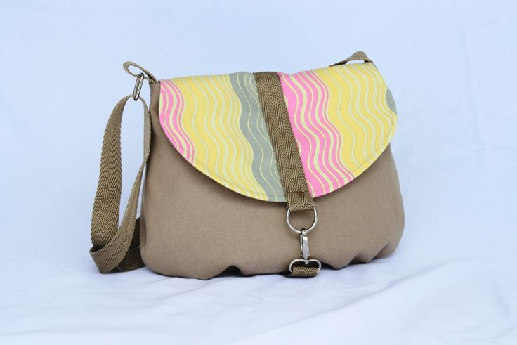 This is a super cute smaller messenger bag with the flap in a contrasting designer fabric by Amy Butler. A smaller sized bag but still big enough to fit all your essentials.It can be worn as a shoulder bag or across the body if you need to be hands free. It features an adjustable strap, spring hook closure and inside pocket.