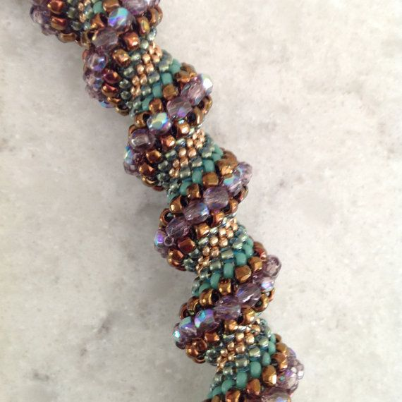 The first in my fall collection of Cellini Spiral Beaded Jewelry, I present this lovely necklace in shades of lavender, teal, copper and rose gold. The colors go with so many outfits, that its hard to pin down a particular color scheme to match. The combination of colors, which is subtle, combines to add sparkle to anything in your wardrobe.  The necklace measures 17 and 1/2 inches in length, and has an antique bronze magnetic closure. There are five different kinds and colors of Japanes...