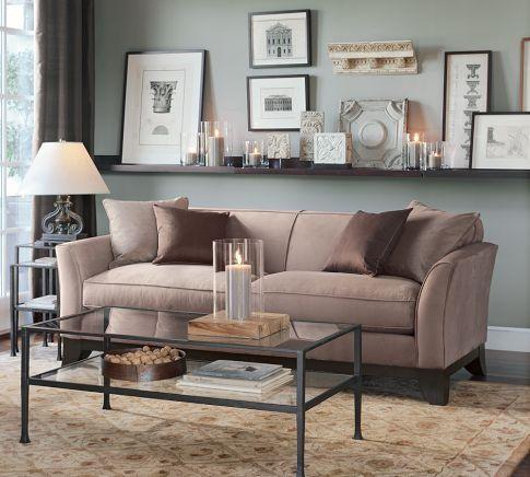 Prateleira única aum pouco mais larga instalada logo acima do sofá. Exibe quadros apoiados, velas entre outros objetos de decoração