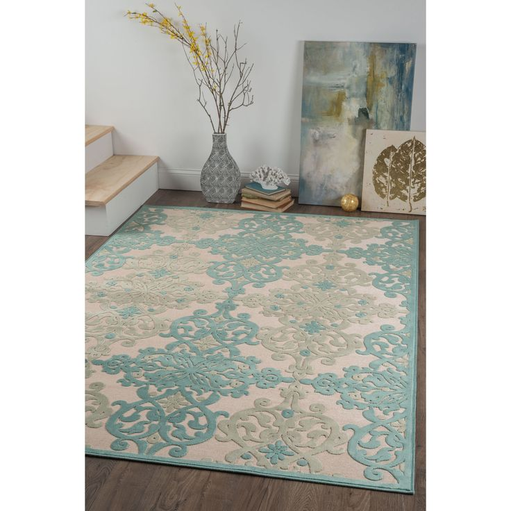 Infuse high style into your home decor with this transitional area rug. Raised chenille scrolling emblems in teal and aqua adorn an ecru background. Made of ultra-soft viscose yarn that is naturally stain-resistant, with cotton backing for a flexible feel
