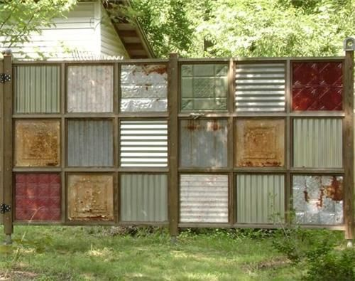 fence made from old pallet wood, and salvaged tin and ceiling panels