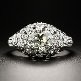 A beautiful bright and sunshiny European-cut diamond, weighing 1.51 carats, glistens and glows from within a lovely gently domed mounting, die-struck and hand-finished in platinum during the peak of the Art Deco period, circa 1925. The ring is appointed throughout with timeless neoclassical design details, a smattering of tiny diamond twinklers, and hand-engraved milgraining, all culminating in a distinctive and distinguished original Jazz Age jewel. The diamond is accompanied by a GIA…