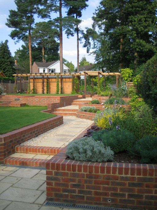a large family garden on a sloping site with retaining walls a water feature