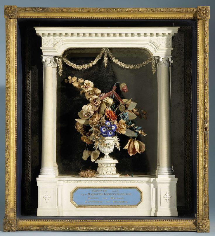 C. Schoon | Bloemvaas onder portiek gewijd aan Lodewijk Napoleon, C. Schoon, c. 1806 - c. 1810 | In een houten kist met versierde en vergulde lijst, achter glas een portiek van papierwerk voor een spiegel. In het portiek een vaas met kunstbloemen. Links naast de vaas een klein papieren nestje waarin enkele eitjes. Op de voet van het portiek het opschrift in gouden letters op blauwe fond. De buitenkant van de kist is geel geverfd, de binnenkant donkerblauw. Aan de keerzijde boven twee…