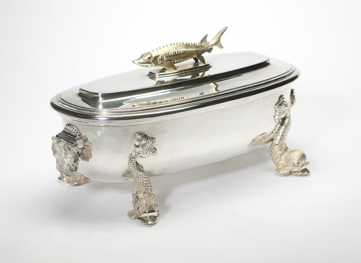 An English sterling silver caviar server, Asprey, 1978, London, with maker's mark and further marked ''Asprey London'', the oblong body with hinged shell-form handles raised on dolphin feet, with inset sterling silver tray with gilt-washed interior, the cover mounted with a gilt sturgeon and fitted to the underside with brackets holding a spoon with a dolphin handle and gilt shell-form bowl.