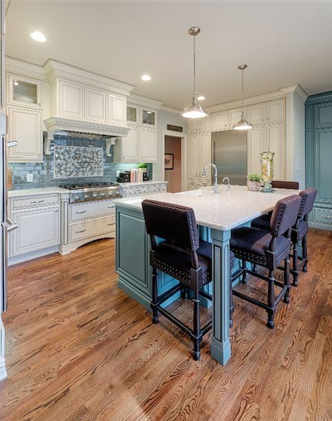 A charming bungalow remodel boasts a bright, eclectic kitchen. Brushed nickel pendant lights from Progress Lighting complement LED recessed can lights for a layered design.