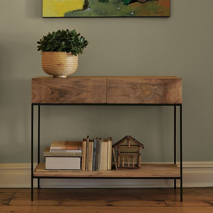Love the warm woods combined with the steel, the clean lines with secret storage. Rustic Storage Console, Raw Mango, $399 from Westelm.com