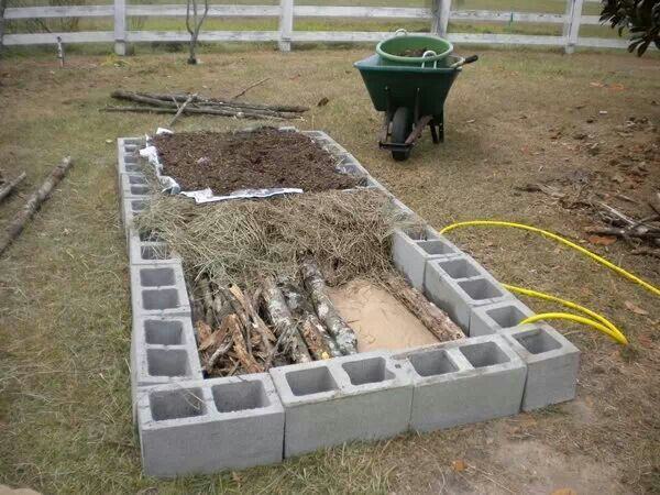Cement blocks raised bed with logs branches and straw - What to put under raised garden beds ...