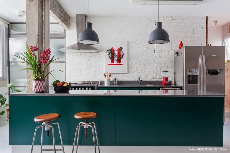 Parede rústica, móveis de cozinha na cor verde, pendentes cinza e banquetas de estilo industrial.