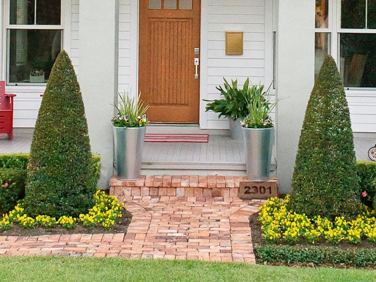 Two sleek planters filled with spiky African irises and yellow, purple, and white pansies flank the front steps. Cone-shaped eugenia topiaries surrounded by beds of yellow pansies flank the walkway.