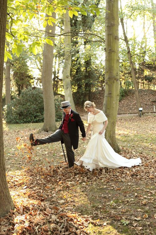 Bride and groom walking through the woods.