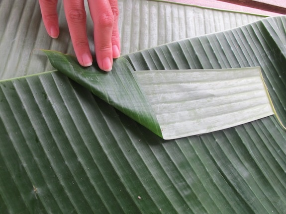 2. Fold the rest of the banana leaf strips into lotus petal shapes (pictured): to make one petal, fold the strip in half horizontally, and then open it flat again. Fold down the top left corner and the top right corner of the strip, which creates a triangle at either end.