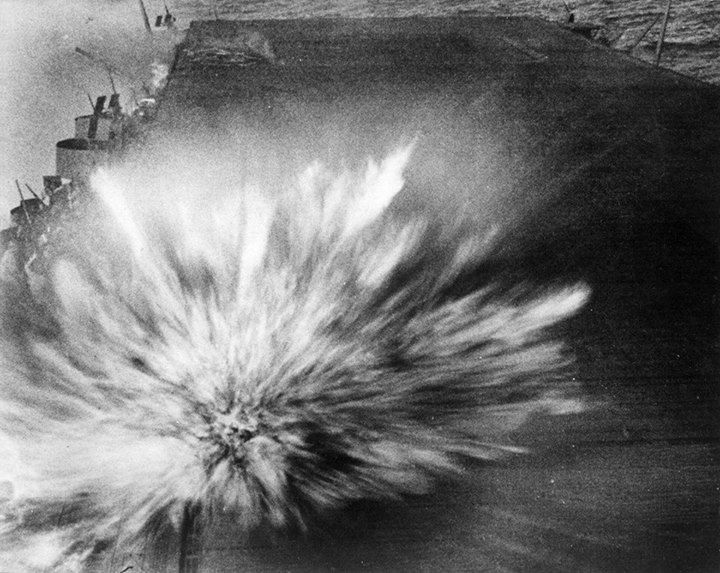 The third and last bomb dropped by an aircraft piloted by Kazumi Horie who died in the attack hits Enterprise causing minor damage. Smoke from the first two bomb hits can be seen in the upper left of the picture.