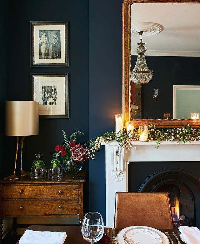 Deep blue walls (in @littlegreenepaintcompany's Basalt Absolute Matt Emulsion) make a good foil for brown furniture, adding a refreshing twist to a traditional table setting. --- #diningroom #fireplace #interior Photograph Jonathan Gooch, design by Emma Collins
