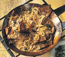 Accompagné d'une sauce à la crème relevée de vinaigre balsamique et de moutarde, le foie de veau à l'oignon, parsemé de sauge fraîche, est un mets délectable.