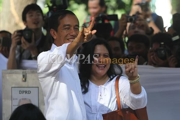 Gubernur DKI Jakarta Joko Widodo atau Jokowi (kiri) bersama istrinya, Iriana, menunjukkan jari mereka yang telah tercelup tinta usai mencoblos di tempat pemungutan suara (TPS) 27, Taman Suropati, Menteng, Jakarta Pusat, dalam Pemilu Legislatif 2014, Rabu (9/4/2014).