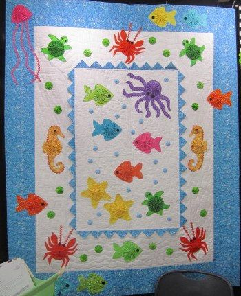 Whimsically cute sea creatures swim around this machine-appliquéd 100% premium cotton quilt, which includes colorful rickrack, buttons, prairie points and yo-yos that add texture and interest to the assortment of octopus, crab, fish, sea horse, turtle, jellyfish, and starfish. The professional longarm quilting design (overall watery bubbles & swirls) adds the perfect finishing touches and makes this great nautical themed quilt perfect for use as a baby crib quilt, toddler lap quilt, or fo...