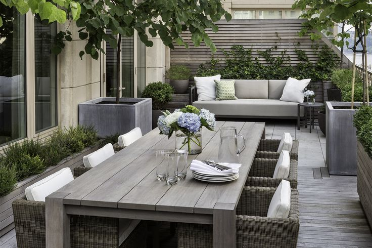 Such a simple use of space, lots of decking in grey with structure planting, white and pale blue tones.