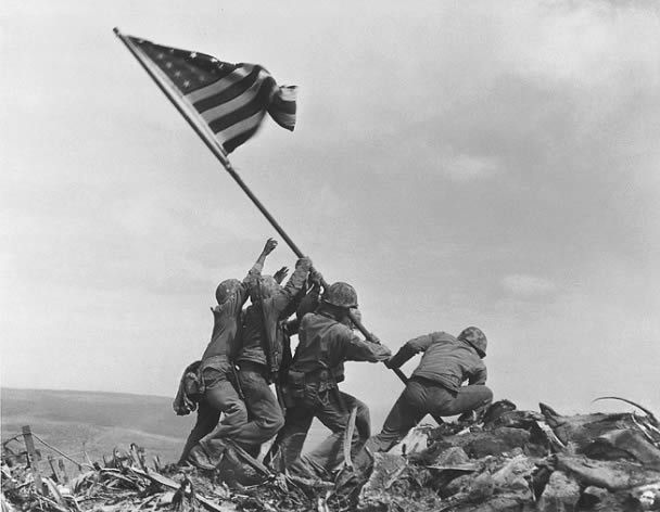 1945 - US Marines from the 28th Regiment, 5th Div, raise the flag of the United States on Mount Iwo Jima