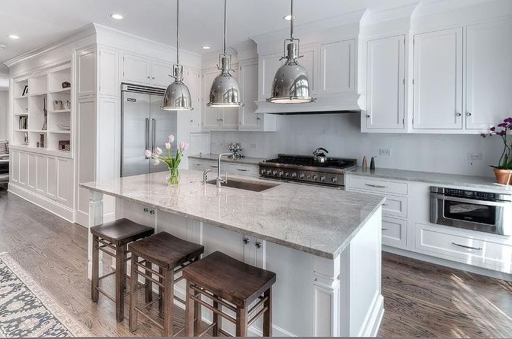 Stunning kitchen features three Restoration Hardware Benson Pendants illuminating white island with legs topped with Super White Granite countertops framing a stainless steel sink and modern spigot faucet lined with wood backless counter stools.
