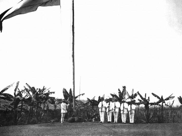 Auf einem Militärstützpunkt in der deutschen Kolonie Kamerun wird von in Tropenanzüge gekleideten Männern eine Fahne gehisst(undatierte Aufnahme aus der Kolonialzeit).Von 1884 bis zum Ersten Weltkrieg war Kamerun eine deutsche Kolonie, dann wurde es 1916 unter Großbritannien und Frankreich aufgeteilt. (picture-alliance / dpa )