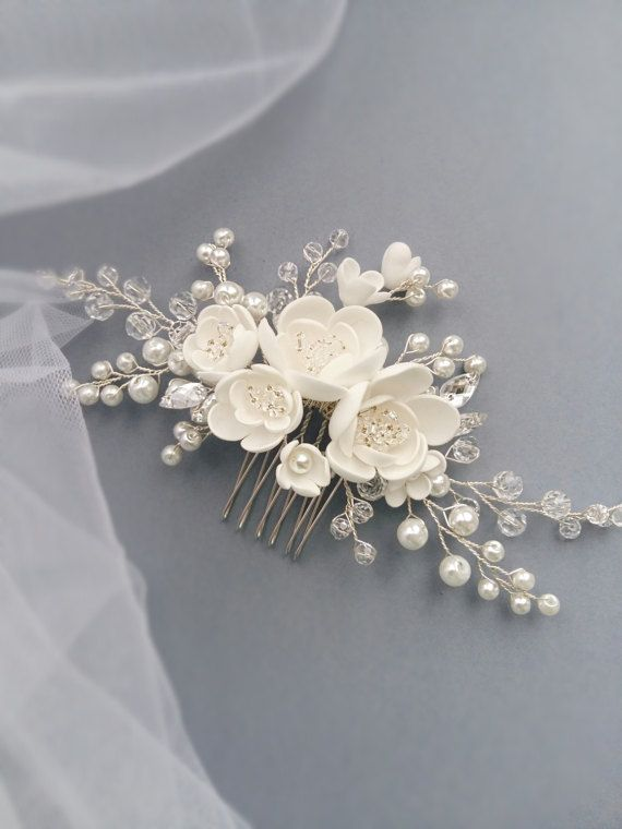 This beautiful handmade bridal hair comb made with pretty crystal elements, handcrafted flowers and white glass pearls. Complement most wedding hairstyles. It is the perfect bridal headpiece for that woman who wants to simply sparkle on her wedding day. DIMENSIONS: 6.5 x 2.5 (16 x 7 cm) (Please note, this does not include the comb itself). Silver, gold or rose gold tone finish. White or Ivory crystal pearls. View my shop for more handmade bridal headpieces: https://www.etsy.com&#...