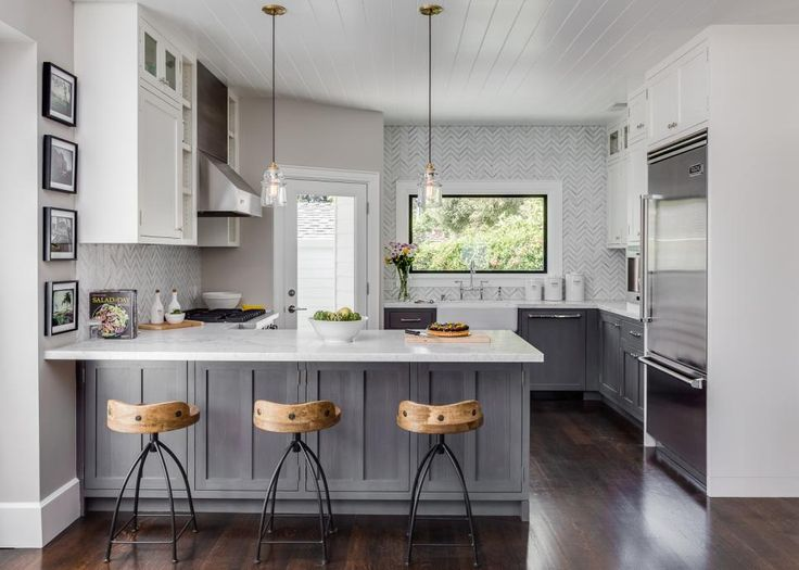 Soft warm gray walls are paired with cool gray base cabinets and a gray-and-white marble backsplash for a fresh take on neutrals.