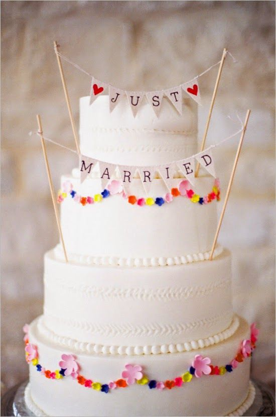 Rustic, floral and colourful themed wedding cake with small 'just married' bunting. For more wedding inspiration visit www.weddingsite.co.uk