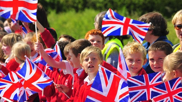 Local schoolchildren in Barkston Ash wave Union Jack flags as they support the Torch Relay on Day 32 of the London 2012 Olympic Torch Relay.