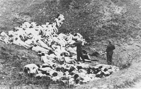 A German policeman shoots individual Jewish women who remain alive in the ravine after the mass execution. (1942)