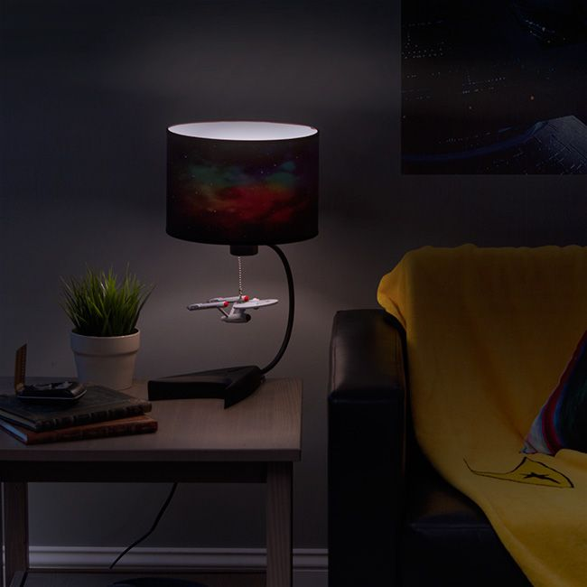 The U.S.S. Enterprise hangs as the lamp pull from a starfield drum lampshade on this Star Trek lamp. The supportive base is a weighty matte black rendering of the the original Star Trek's command insignia.