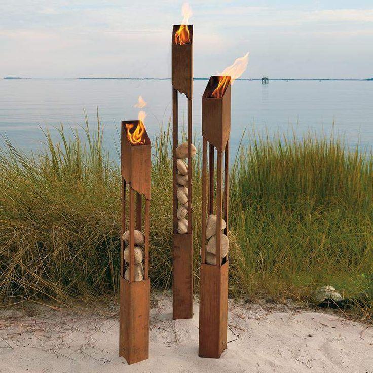 flambeaux décoratifs en acier Corten et pierres dans le jardin
