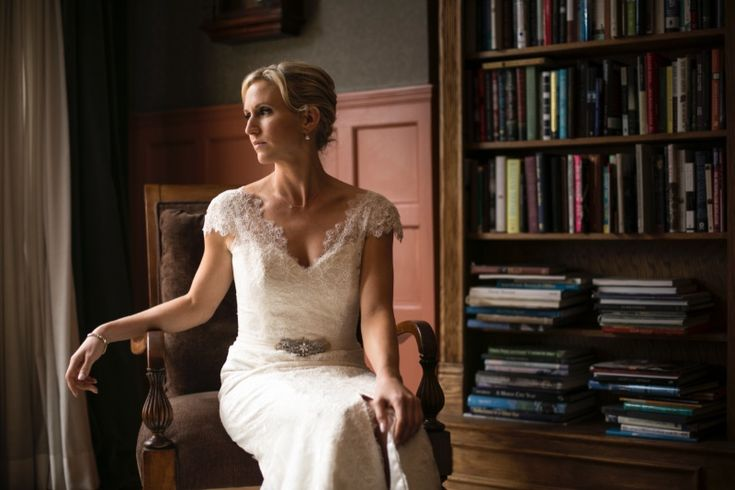 A sophisticated bride posing on her wedding day in a  gorgeous Amy Kuschel bridal gown from The Gown Shop - Ann Arbor.