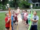 """Wet noodle. Tape a cup full of water to the top of a pool noodle. I'd tape a """"hold here"""" on the noodle. The kids race to pass it up and down the line without spilling the water. This link is broken, but it's pretty self explanatory."""