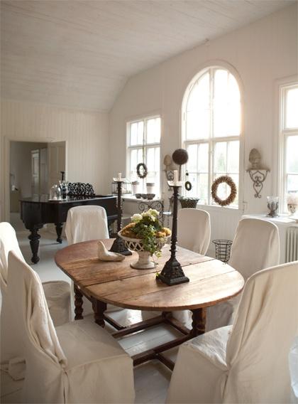 Den gamla gymnastiksalens takhöjd och ståtliga fönster ger underbar rymd till det kombinerade mat- och vardagsrummet. Bordet är ett barockslagbord från sent 1600-tal. Stolarna som Ellens dotter sytt överdrag till kommer från en italiensk matsalsgrupp.