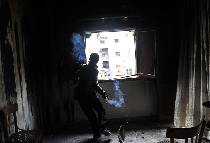 A rebel fighter throws a homemade grenade towards Syrian government forces through a window at a flat in the Salaheddine neighbourhood of Aleppo on February 16, 2013. More than 300 people were abducted by armed groups in northwestern Syria over two days in an unprecedented string of sectarian kidnappings, a watchdog and residents said. AFP PHOTO/BULENT KILIC