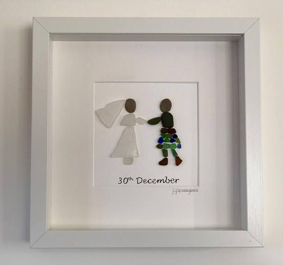 *This is a customer order*. This beautiful picture depicts a bride and groom on their wedding day. The happy couple have been created using sea glass and beach pebbles. The brides veil has a lovely delicate pattern, very similar to lace. The grooms kilt is created using small pieces of