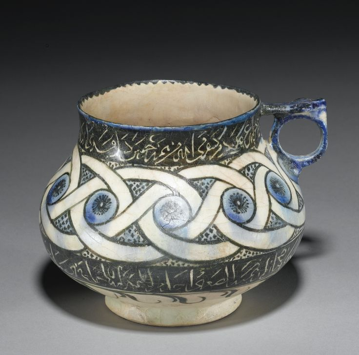 A KASHAN CUP PAINTED WITH CALLIGRAPHIC BANDS, PERSIA, EARLY 13TH CENTURY of squat globular form on short foot with straight rim and small loop handle with palmette-form thumb-rest, the exterior decorated in underglaze blue and black with an abstract design of entwined bands between two calligraphic friezes written in reserve against a black ground