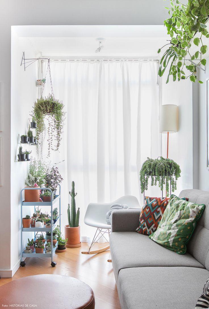Sofá cinza, almofadas estampadas e carrinho de ferro para colocar plantas.