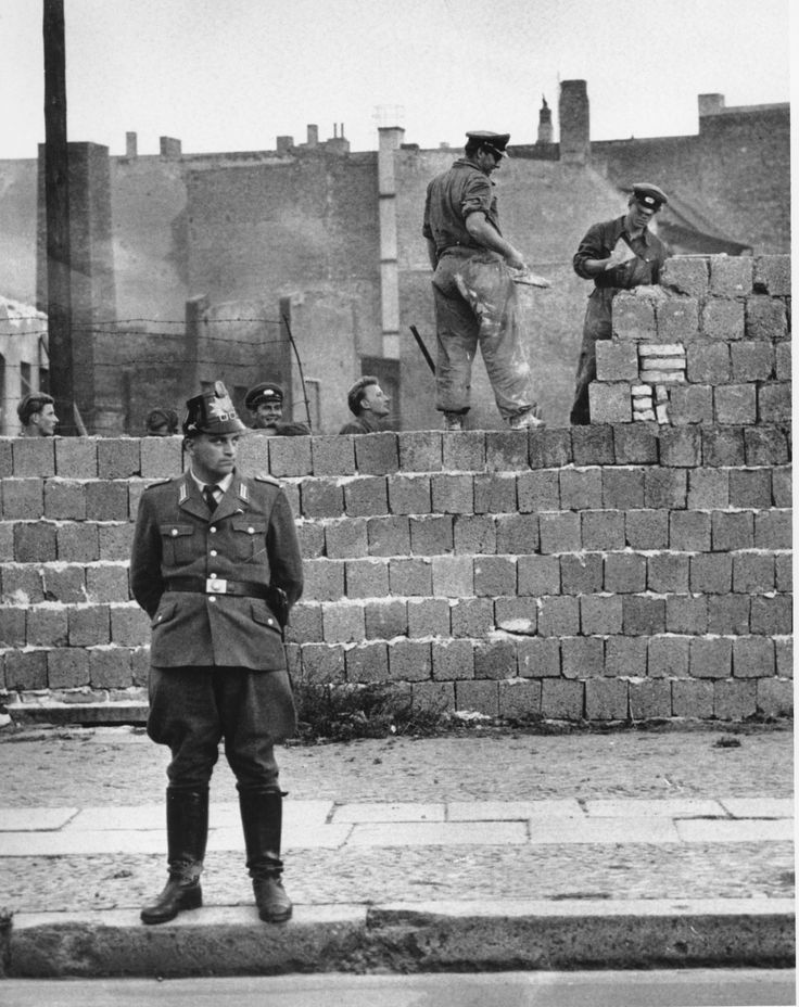 A West Berlin guard stands in front of the concrete wall dividing East and West Berlin at Bernauer Strasse as East Berlin workmen add blocks to the wall to increase the height of the barrier, Oct. 7, 1961. (AP Photo) PA-3389235