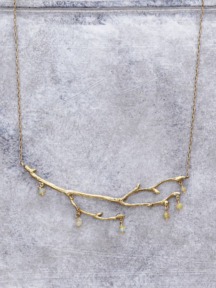 The faeries have an offering for you. This stunning golden necklace features an organic branch dripping with fiery opalescent gems. Will you accept this gift from the enchanted realms? Shown in Bronze