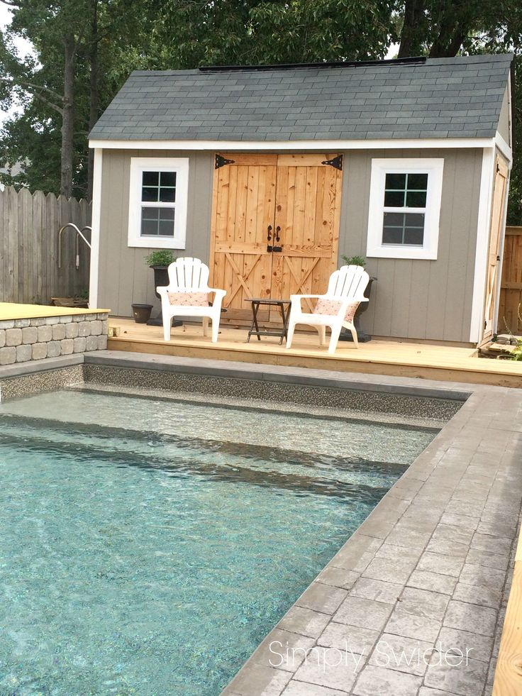 Traditional pool with tanning ledge and colonial style pool house. I love the cedar barn doors!