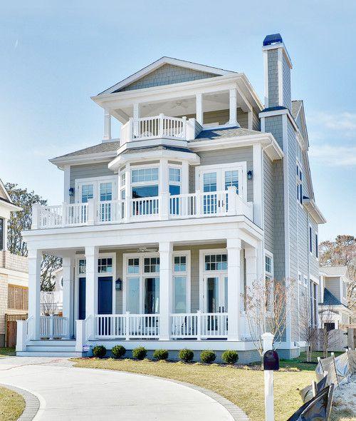 Dark gray siding, white trim, blue front door, three porches. Silver Lake vacation home, DE. Echelon Custom Homes.