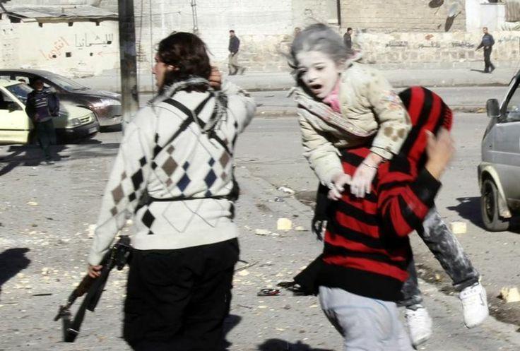 9 décembre. Un homme transporte une jeune fille blessée dans les rues d'Alep, en Syrie, suite à une frappe aérienne des forces loyales à Bachar Al-Assad selon des militants. Photo stringer / Reuters